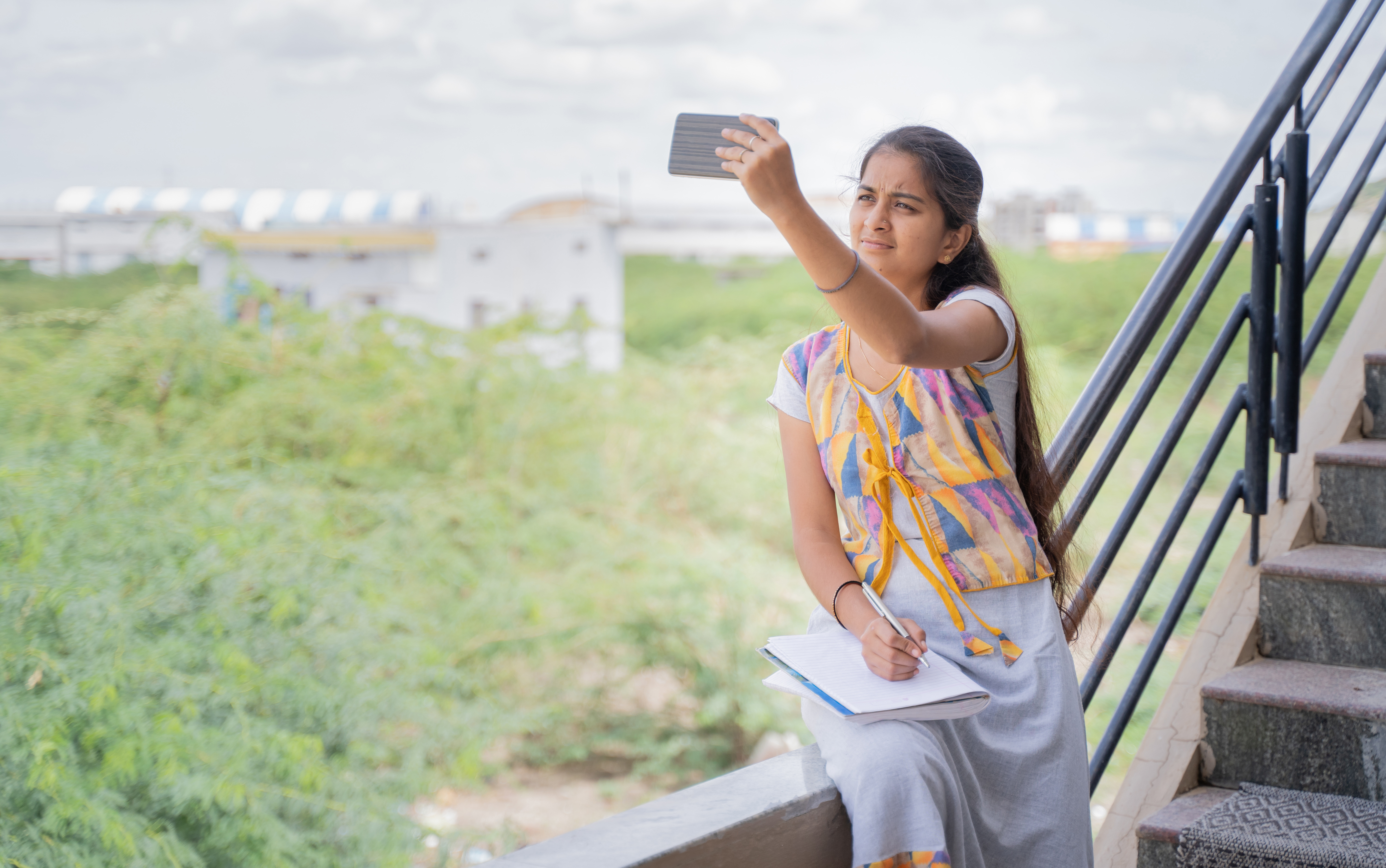 College girl outside home watching online class due to slow internet connection - concept of network issue at remote places and problem of virtual class or distance learning during pandemic